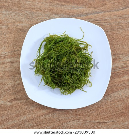 Fresh seaweed salad on white plate against wooden background, top view - stock photo