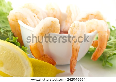 fresh shrimp cocktail with sauce, lemon wedges, and garnished with crispy romaine lettuce - stock photo