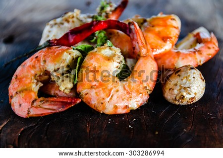 fresh shrimps served on a wood plate with garlic onion and chili - stock photo