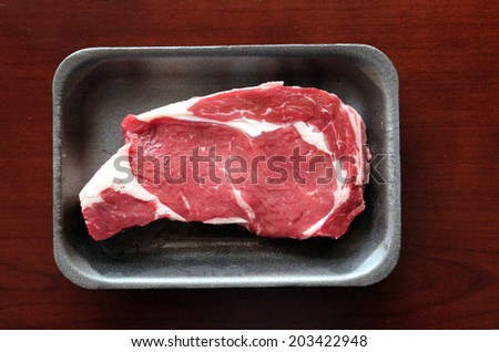 Fresh sirloin beef steak in packaging tray.   - stock photo