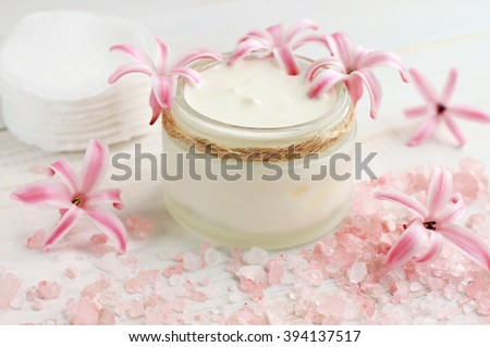 Fresh skin care cream, flowers, pink bath salt, cotton pads. Natural beauty treatment.