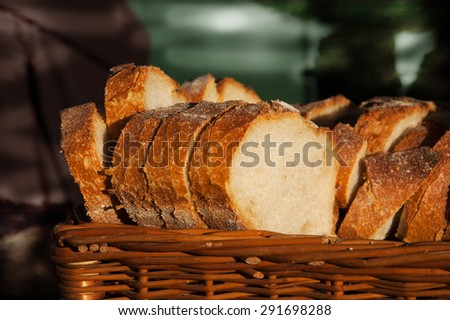 Fresh sliced bread in a wicker basket in dark interior. A game of light and shadow. - stock photo