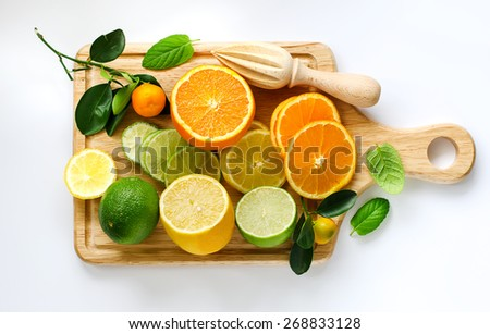 Fresh sliced citrus fruits on cutting board with wooden squeezer - stock photo