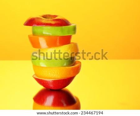 Fresh sliced fruit on colorful background - stock photo