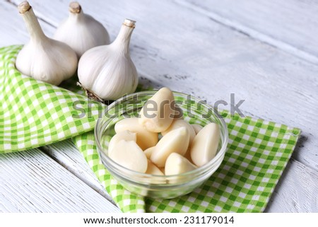 Fresh sliced garlic in glass bowl on wooden background - stock photo