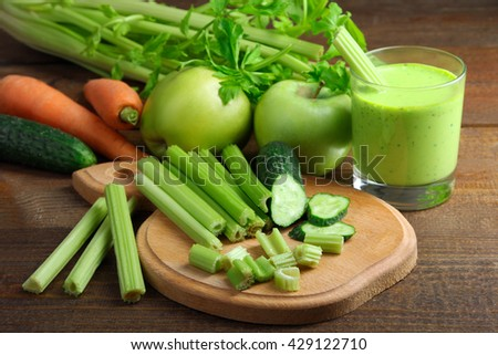 Fresh sliced green celery on wooden cutting Board with cucumber near juice in a glass and a pile of vegetables on brown wooden background - stock photo