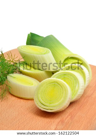 Fresh sliced leeks and dill on a wooden board isolated on white - stock photo