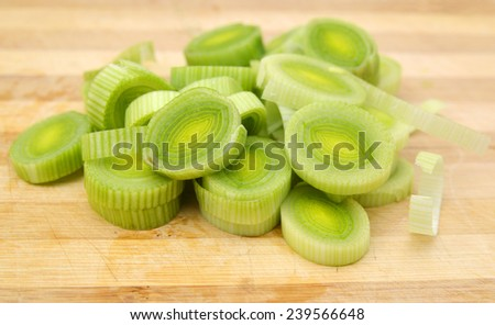 Fresh sliced leeks and dill on a wooden board isolated on white