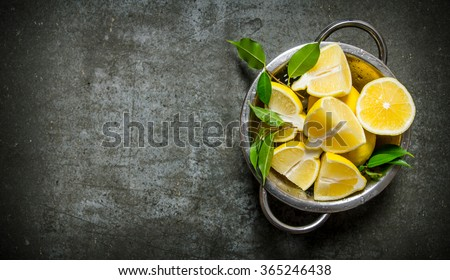 Fresh sliced lemons with leaves in a saucepan. On the stone table. Free space for text . Top view - stock photo