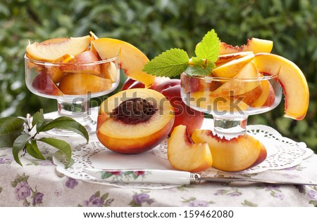 Fresh sliced �¢??�¢??peaches in glass bowls against a green garden