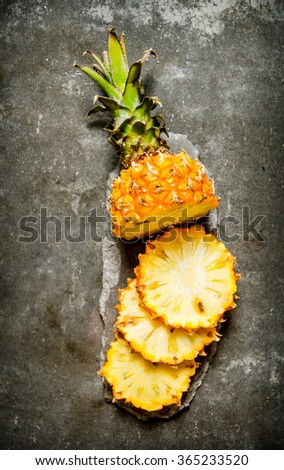 Fresh sliced pineapple on a stone stand. On the stone table. Top view - stock photo
