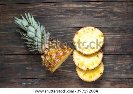 Fresh sliced pineapple on a wood table. Top view. - stock photo