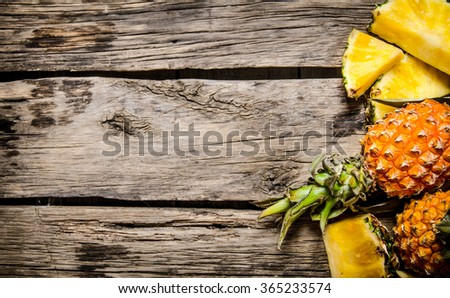 Fresh sliced pineapple with whole. On the wooden background. Free space for text . Top view - stock photo