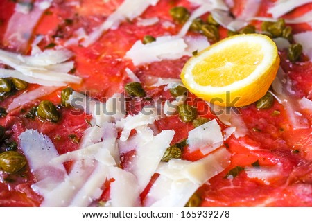 Fresh Sliced raw beef meat with lemon on the table  - stock photo