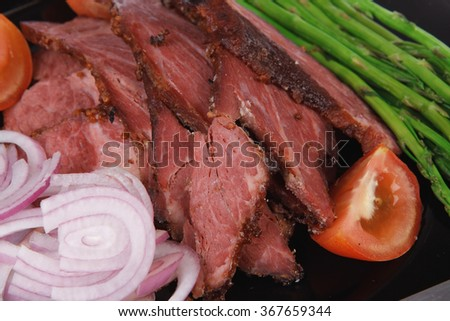 fresh sliced roast beef on black plate with cutlery and asparagus isolated on white background - stock photo