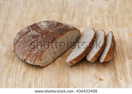 Fresh sliced rye bread on a rustic wooden table - stock photo