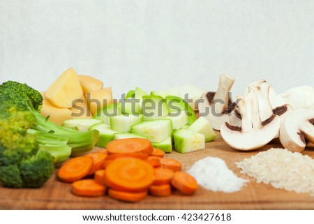 Fresh sliced soup ingredients on wooden cutting board. Side view, low aperture shot, selective focus - stock photo