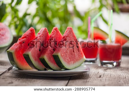 fresh sliced watermelon and watermelon smoothie on a wooden table - stock photo