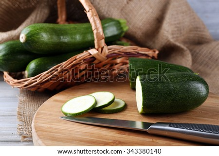 Fresh sliced zucchini on cutting board, on wooden background - stock photo