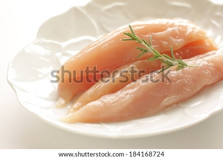 Fresh slices of chicken displayed on a white plate with a sprig on top. - stock photo