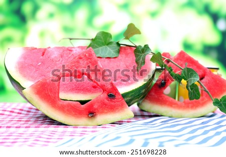 Fresh slices of watermelon on table, on nature background - stock photo