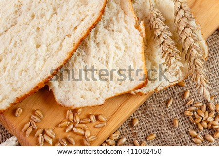Fresh slices whole bread and wheat on the wooden board on burlap - stock photo