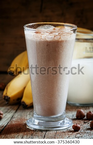 Fresh smoothie banana and chocolate, milk and nuts in a large glass on the old wooden background, selective focus