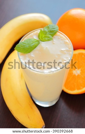Fresh smoothie with banana and orange fruits in a glass - stock photo