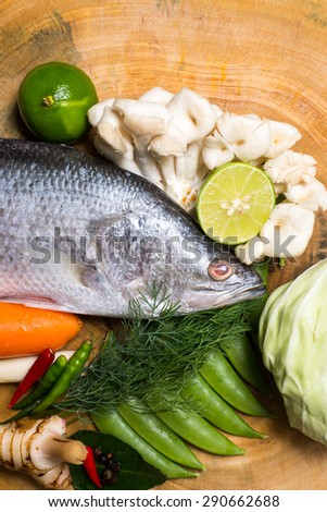 fresh snapper with aromatic herbs, spices and vegetables on a cutting board - stock photo
