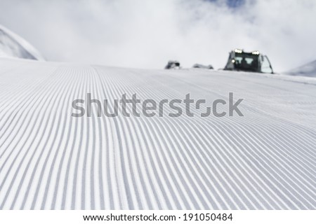 Fresh snow groomer tracks on a mountain ski piste - stock photo