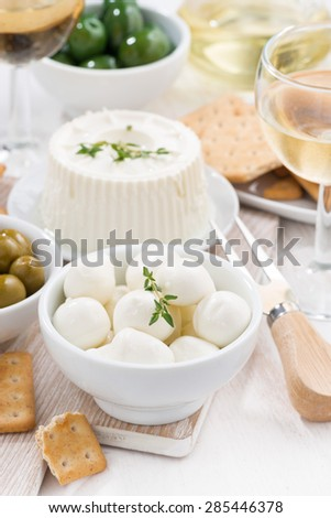 fresh soft cheeses, crackers and pickles to wine, vertical, top view - stock photo