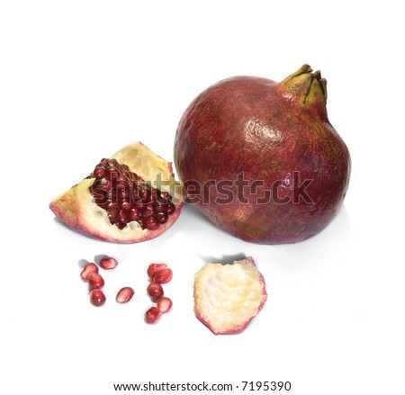 Fresh solid pomegranate with parts of other one and seeds around in white background