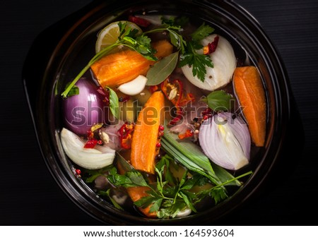 Fresh soup in a pot on black background - stock photo