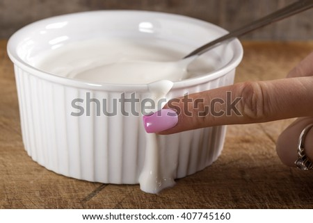 Fresh sour cream in white bowl and female finger on wooden background - stock photo