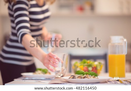 Fresh spaghetti with creamy mushroom sauce and basil leaf in home interior