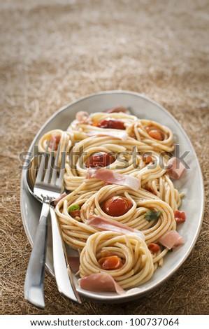 Fresh spaghetti with prosciutto and tomato sauce close up - stock photo
