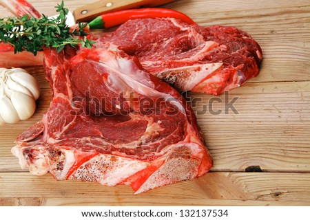 fresh spare ribs : raw lamb with thyme , garlic and red chili pepper on wooden board - stock photo