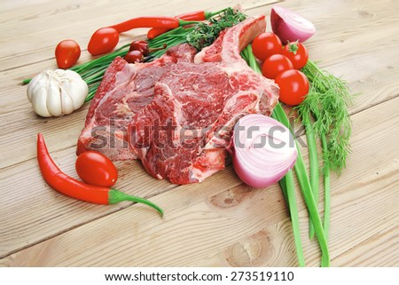 fresh spare ribs : raw lamb with thyme , red chili pepper , tomato , garlic , and chives over wooden table - stock photo