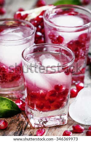 Fresh sparkling water with ice and pomegranate, selective focus