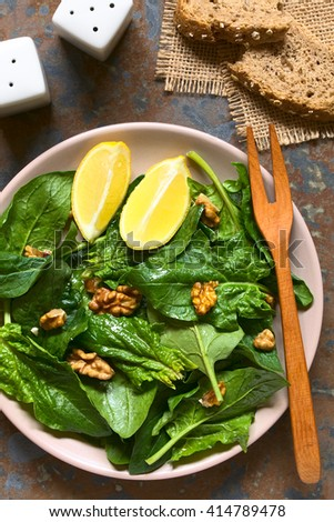 Fresh spinach and walnut salad with lemon wedges on the side served on plate, photographed overhead on slate with natural light