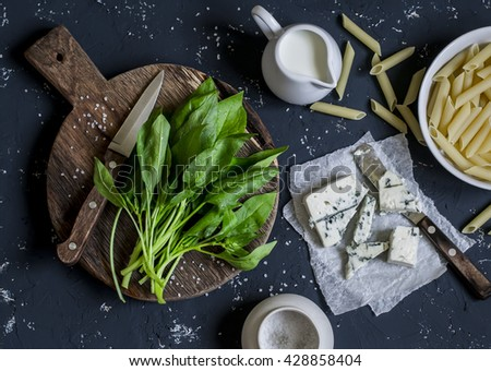 Fresh spinach, dry pasta, blue cheese, cream - raw ingredients for cooking pasta with spinach, blue cheese cream sauce. On the dark stone surface. Top view - stock photo