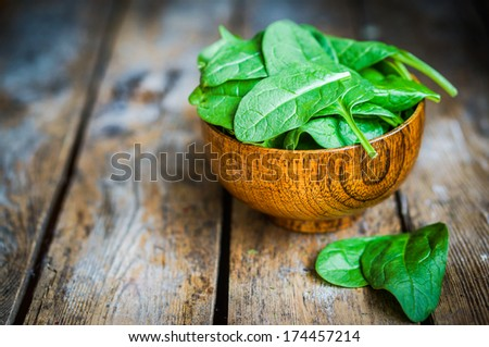 Fresh spinach in a bowl on rustic wooden background - stock photo