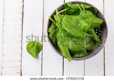 Fresh spinach in old bowl on white wooden background. Selective focus, horizontal. Top view. - stock photo