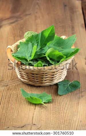 Fresh spinach leaves in a basket - stock photo