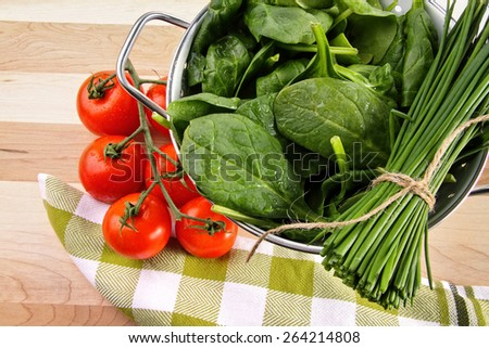 Fresh spinach leaves with tomatoes and strainer - stock photo