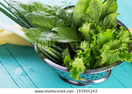 Fresh spinach, salad, onion, fennel, salad in metal bowl on wooden table. Selective focus, horizontal.