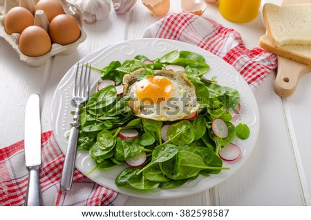 Fresh spinach salad with fried egg and radish, white board, white bread, bio eggs