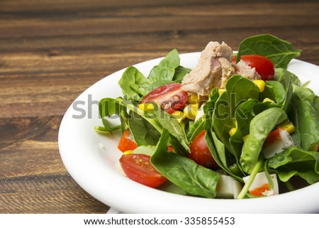 Fresh spinach salad with tuna and corn, small pieces of cherry tomatoes in white plate on wooden table