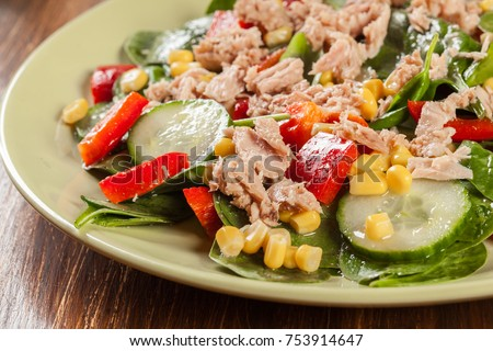 Fresh spinach salad with tuna, cucumber, corn, and red paprika on a plate. Healthy raw food concept.