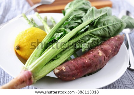 Fresh spinach with lemon and sweet potato on white dish - stock photo